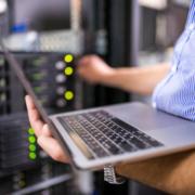 ingénieur en serveur informatique avec son ordinateur devant les serveurs